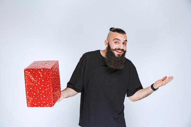 Мужчина с бородой держит свою красную подарочную коробку, наслаждается ею и чувствует себя счастливым.