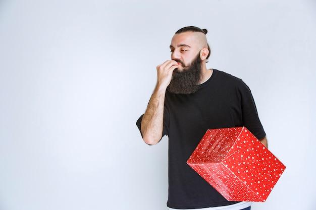 그의 빨간 선물 상자를 들고 그것을 즐기고 행복 한 느낌 수염을 가진 남자.