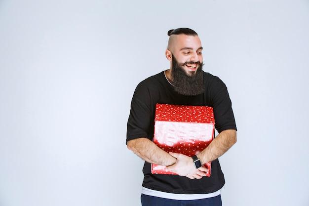 Uomo con la barba che tiene la sua confezione regalo rossa, si diverte e si sente felice.
