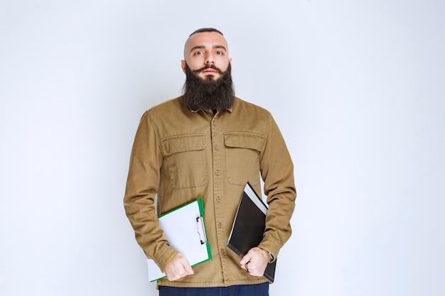 Мужчина с бородой держит свой список отчетов и с уверенностью ждет.