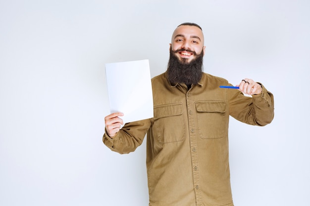 Uomo con la barba che tiene la sua lista di rapporti e aspetta con fiducia.