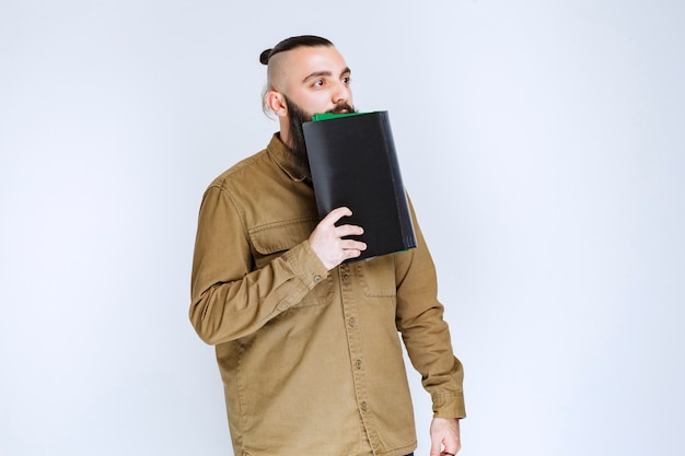 Man with beard holding his report list and waiting with confidence.