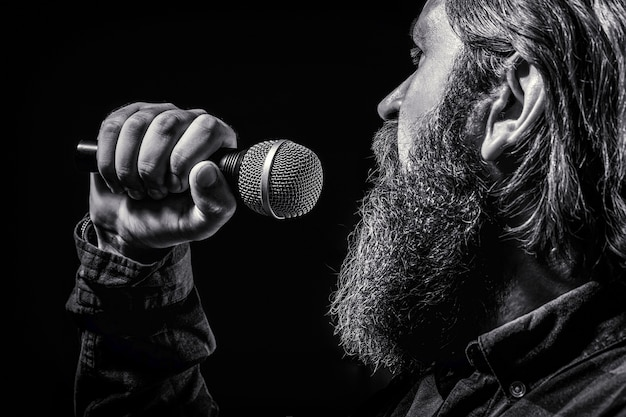 Man with a beard holding a microphone and singing. bearded man in karaoke sings a song into a microphone. male attends karaoke. black and white.