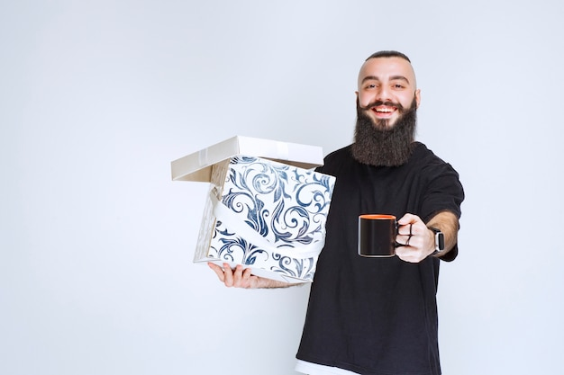 Uomo con la barba che tiene una scatola regalo blu aperta con una tazza di caffè e sembra felice.