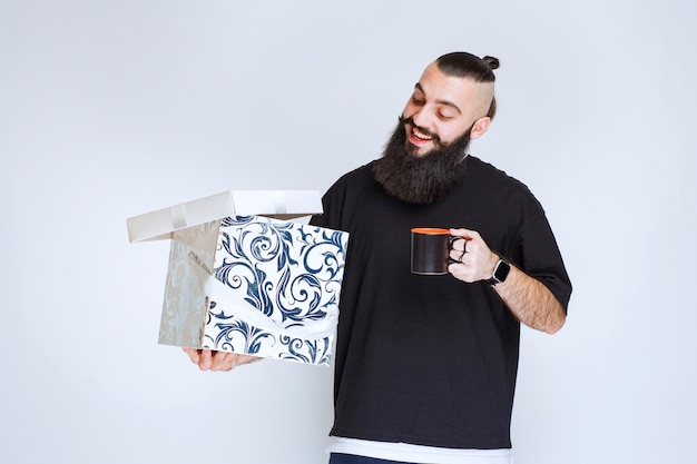 Man with beard holding an open blue gift box with a cup of coffee and looks happy.