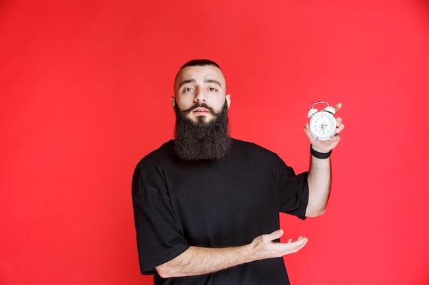 Uomo con la barba che tiene e promuove una sveglia come prodotto.