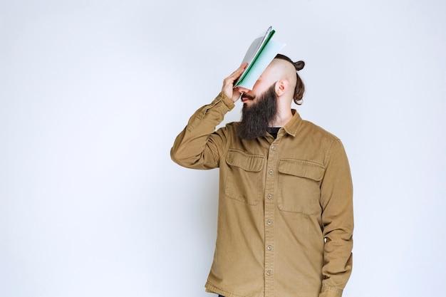 Uomo con la barba che tiene un quiz e sembra confuso e pensieroso.