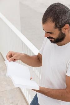 Uomo con la barba che tiene e libro di lettura all'aperto