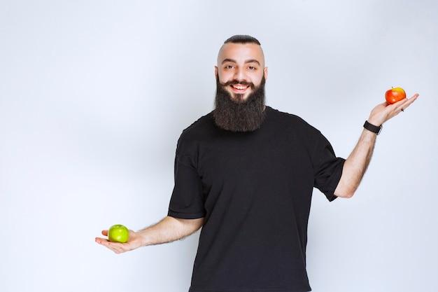 Человек с бородой, держа в руке красные и зеленые яблоки.