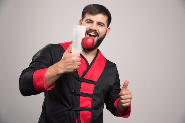 Человек с бородой держит красное яблоко на ноже.