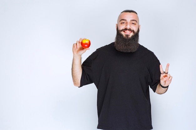 Man with beard holding a red apple or peach and enjoying the taste.