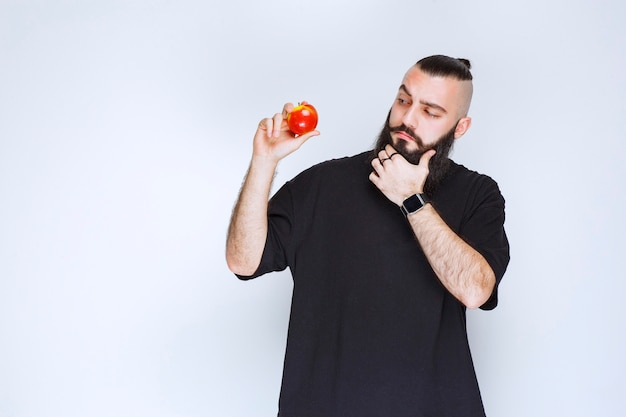 Man with beard holding a red apple or peach and thinking.