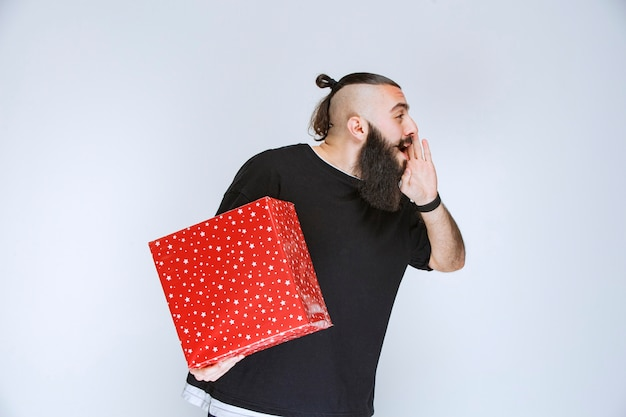 Man with beard holding a red gift box and calling someone or whispering.