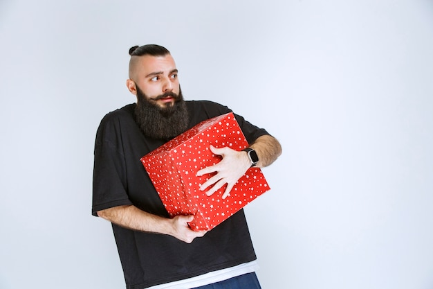 Man with beard holding a red gift box and looks confused and terrified.