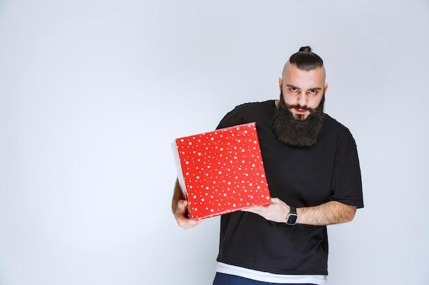 Uomo con la barba che tiene una confezione regalo rossa