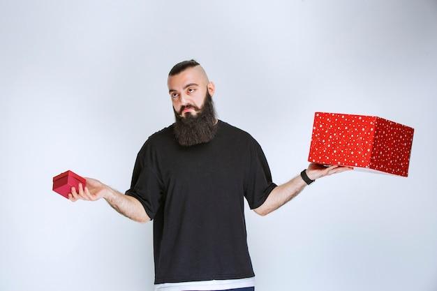 빨간색 선물 상자를 들고 choise 만들기에 대해 주저 수염을 가진 남자.