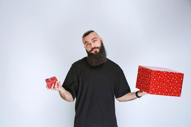 Мужчина с бородой держит красные подарочные коробки и не решается сделать выбор.