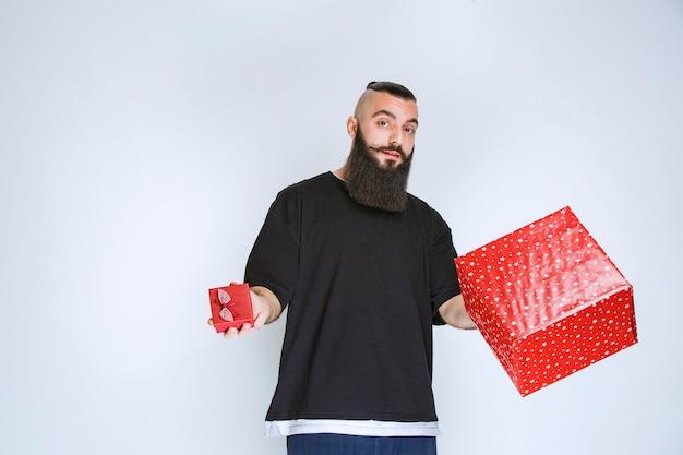 Uomo con la barba che tiene scatole regalo rosse con entrambe le mani e prende una decisione.
