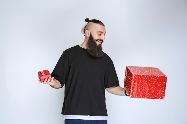 Man with beard holding red gift boxes in both hands and making a decision.