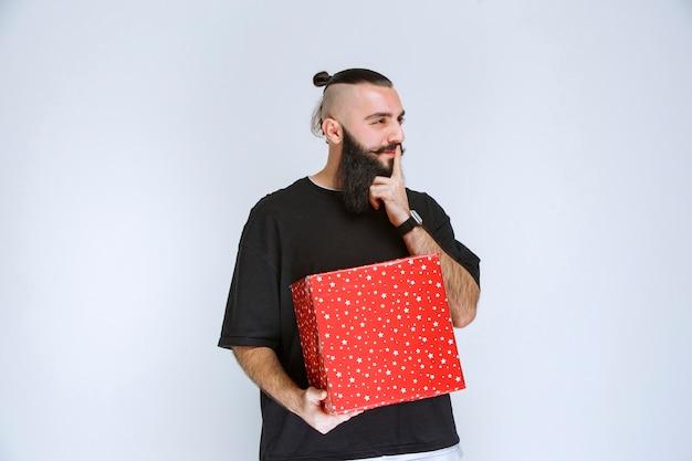 Uomo con la barba che tiene in mano scatole regalo rosse ed esita a fare una scelta.