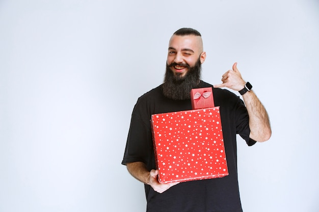 Man with beard holding red gift boxes and pointing behind.