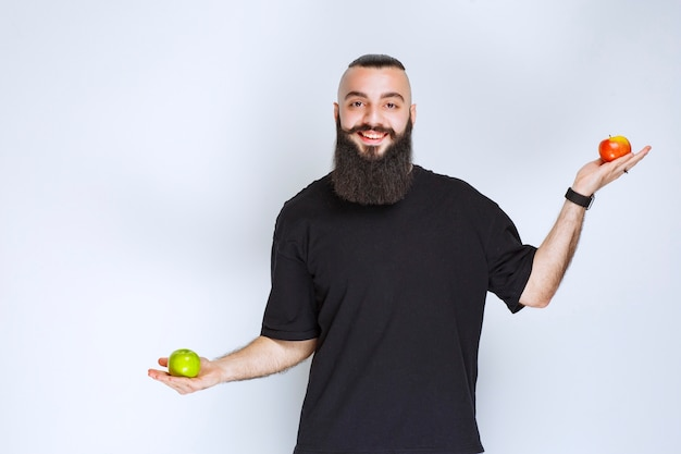 Man with beard holding red and green apples in the hand.