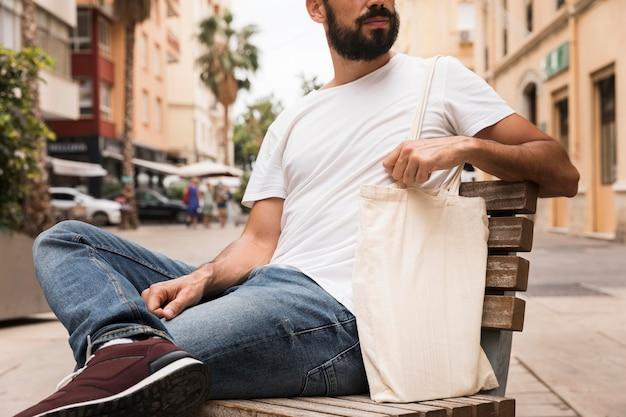 Мужчина с бородой держит сумку для покупок
