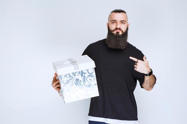 Uomo con la barba che tiene in mano una confezione regalo blu bianca e lo dimostra.