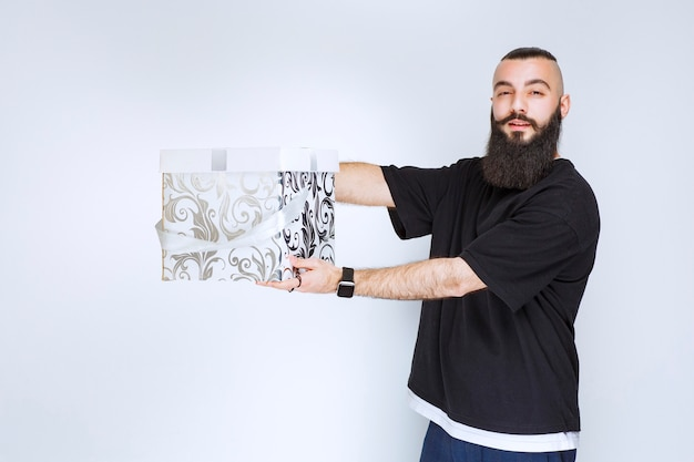 Man with beard holding a white blue gift box and demonstrating it.