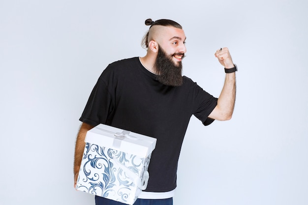 Man with beard holding a white blue gift box and feeling successful.