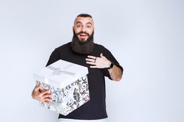 Uomo con la barba che tiene in mano una confezione regalo blu bianca e sembra sorpreso.