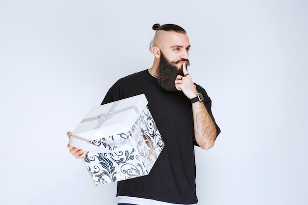 Man with beard holding a white blue gift box pointing his mouth and asking for silence.