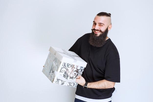 Uomo con la barba che tiene in mano una confezione regalo blu bianca che sorride e si sente felice.