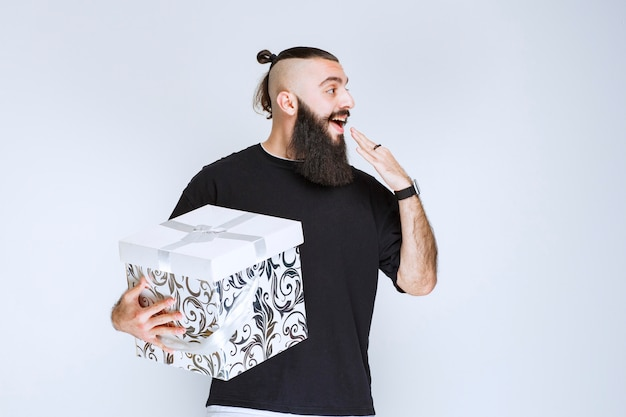 Man with beard holding a white blue gift box smiling and feeling happy.