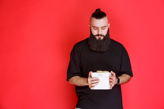 Man with beard holding a white gift box and looks doubtful about what is inside.
