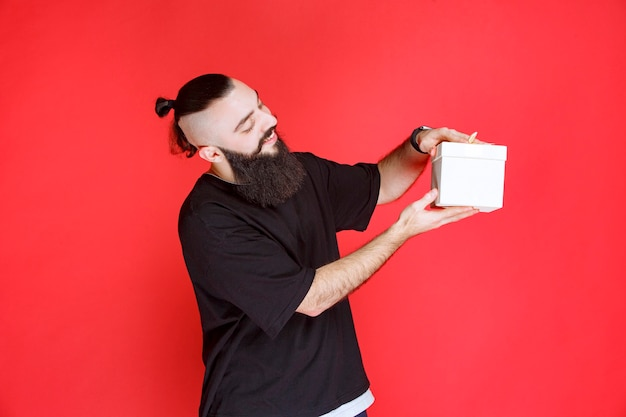Man with beard holding a white gift box with satisfaction.