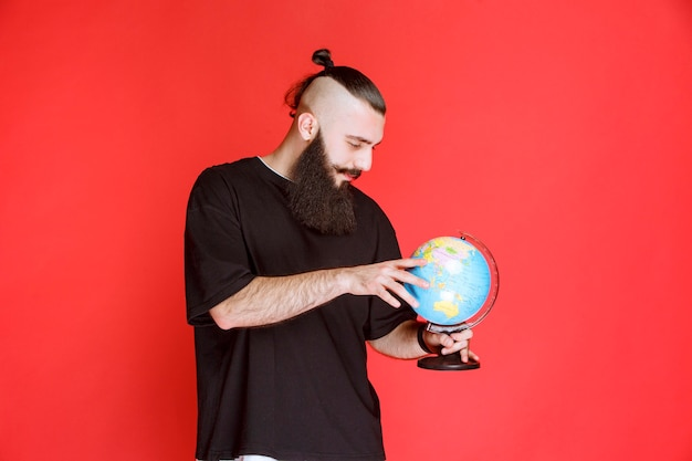 Man with beard holding a world globe and looking for places over it.