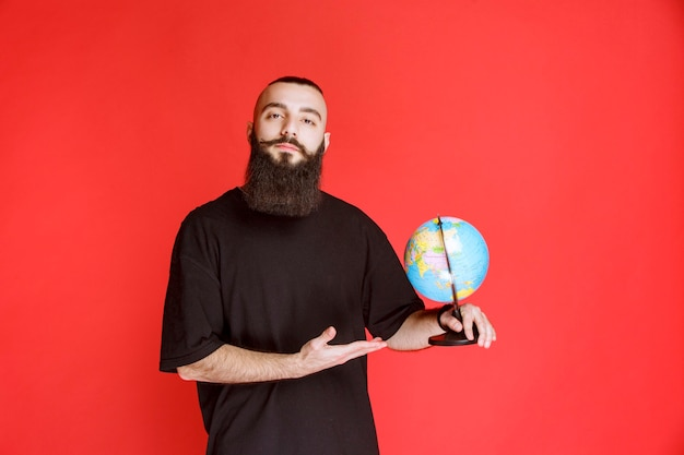 Man with beard holding a world globe.