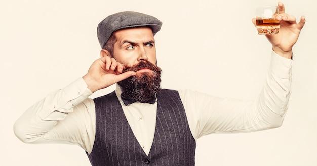 あごひげを生やした男はガラスのブランデーを保持しています。あごひげを生やしたドリンクコニャック。ソムリエは飲み物を味わいます。ウイスキーのグラスを持っている男。ウイスキーをすすりながら。厚いひげを持つ男の肖像画。マッチョな飲酒。デグステーション、テイスティング