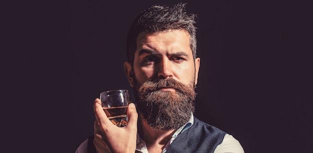あごひげを生やした男はガラスのブランデーを保持しています。ひげを生やした飲み物のコニャック。