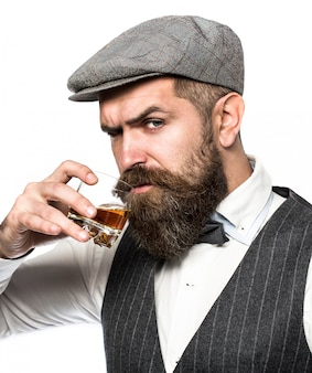 Man with beard holds glass brandy. bearded drink cognac.