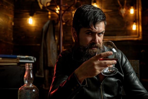 Мужчина с бородой держит стакан бренди. мачо пьёт. дегустация, дегустация. красивый стильный бородатый