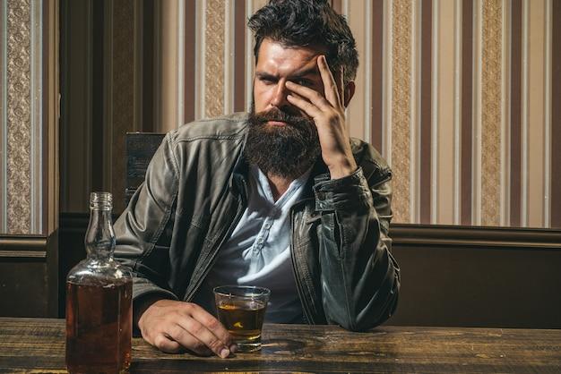 あごひげを生やした男はガラスのブランデーを保持しています。ウイスキーのグラスを持っている男。ハンサムなスタイリッシュなひげを生やした男は仕事の後に家で飲んでいます。