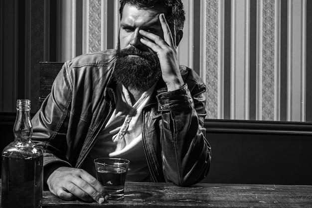 あごひげを生やした男はガラスのブランデーを保持しています。ウイスキーのグラスを持っている男。ハンサムでスタイリッシュなひげを生やした男は