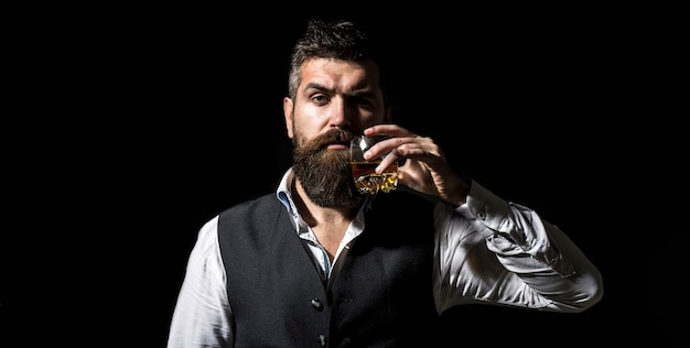 Man with beard holds glass of brandy. tasting and degustation concept
