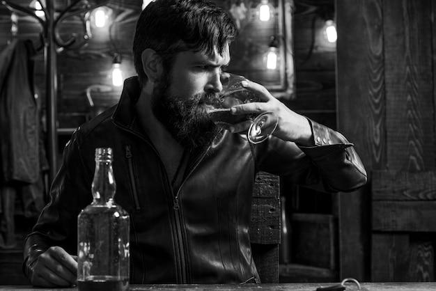 Man with beard holds glass brandy.