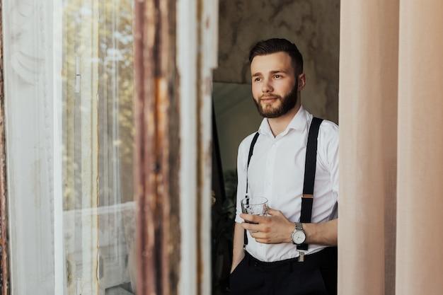 Мужчина с бородой держит стакан бренди.