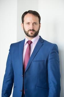 青いジャケット、シャツ、ネクタイのひげを持つ男。ビジネスマンやマネージャーが壁にポーズをとる。ビジネス、起業家精神の概念。キャリア、職業、仕事。ファッション、スタイル、ドレスコード。