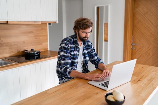 キッチンでラップトップを使用して格子縞のシャツのひげを持つ男。