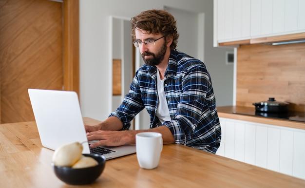 Человек с бородой в клетчатой рубашке, используя ноутбук на кухне.